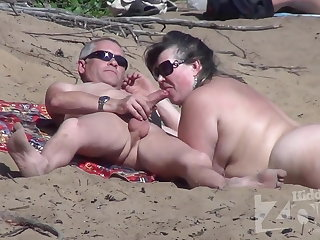 Blowjob on a nudist beach.